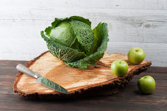 Whole cabbage and apples on rough wooden chopping board Royalty Free Stock Images