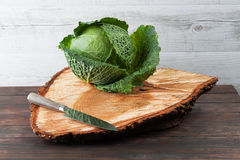 Whole cabbage on rough wooden chopping board Stock Images