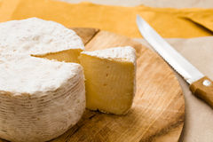 Whole caciotta cheese with slice over chopping board and knife Royalty Free Stock Image