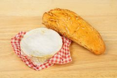 Camembert and bread. Whole camembert cheese and a crusty bread roll on a wooden chopping board royalty free stock photo