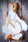 Whole Camembert cheese and portion. On olive cutting board Stock Photo