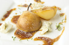 Whole caramelized pear with gorgonzola Stock Photography