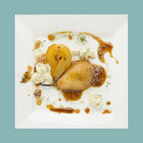 Whole caramelized pear with gorgonzola and thyme  on white plate Stock Images