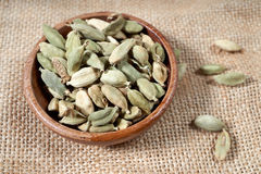 Whole Cardamom capsules. Whole cardamom seeds in a small wooden bowl Stock Photos