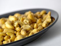 Whole Cashews. Some whole cashews in a black plate royalty free stock images