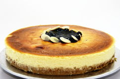 Whole Cheesecake. Cheese cake top with blueberry jam and sliced almond Royalty Free Stock Photos