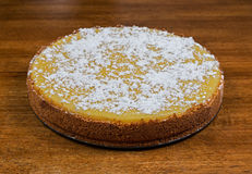 A whole cheesecake resting on a table Royalty Free Stock Photo
