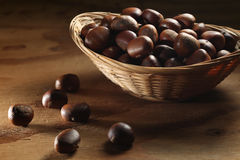 Whole chestnuts in basket. Whole chestnuts with shells in a wicker basket Stock Photography