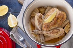 The whole chicken baked with lemon and rosemary in a red cast iron. Blue wooden background and gray towel. Knife and fork. Free royalty free stock images