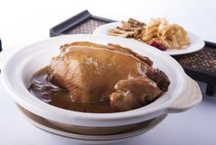 Whole chicken and chinese herbs in pot royalty free stock image
