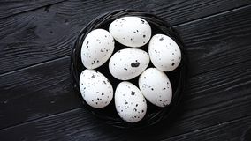 Whole Chicken eggs in a nest on a black rustic wooden background. Easter symbols. Or Healthy food concept stock footage