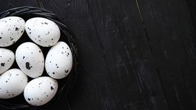 Whole chicken eggs in a nest on a black rustic wooden background. Easter symbols. Or healthy food concept stock video footage