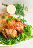 A whole chicken grilled with fresh vegetables and herbs filed on. Grilled chicken on a white plate with fresh herbs and lemon Stock Image