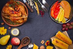 Whole chicken or turkey, fruits and grilled autumn vegetables: corn, pumpkin, paprika. Thanksgiving Day food concept. Harvest or Thanksgiving background. View Stock Photo
