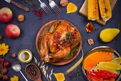 Whole chicken or turkey, fruits and grilled autumn vegetables: corn, pumpkin, paprika. Thanksgiving Day food concept. Harvest or Thanksgiving background. View Royalty Free Stock Image
