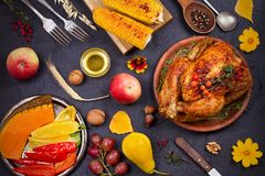 Whole chicken or turkey, fruits and grilled autumn vegetables: corn, pumpkin, paprika. Thanksgiving Day food concept. Harvest or Thanksgiving background. View Royalty Free Stock Photography