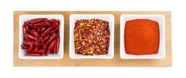Whole chili pepper, chili flakes and cayenne powder on white background Stock Photo