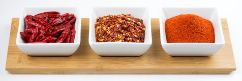 Whole chili peppers, flakes, and chili powder isol Stock Image