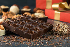 Whole chocolate bar with chocolate candies and gift box Stock Photos
