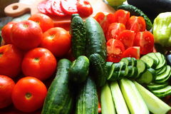 Whole and chopped tomatoes and cucumbers. Are on the table whole and chopped tomatoes and cucumbers Stock Photos