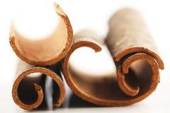 Whole cinnamon sticks against a white background. Whole cinnamon sticks shot in a creative abstract manner against a white background Stock Photos