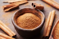 Whole cinnamon sticks and powder on brown rustic background. Aromatic spices. Royalty Free Stock Photos