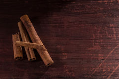 Whole cinnamon sticks on wooden background Stock Images