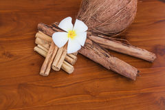 Whole coconut, cinnamon sticks and flower on wooden brown table. Close-up Stock Photo