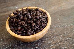 Whole coffee beans in a bamboo bowl on a wooden background Stock Images