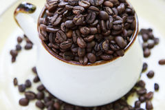 Whole Coffee Beans in a Mug Royalty Free Stock Images