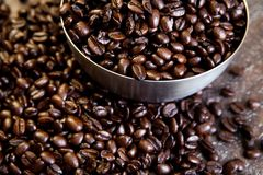 Whole coffee beans in a stainless steel bowl on a wooden table Stock Images