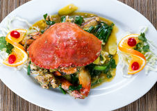 Whole cooked Dungeness crab with green onion sauce on white serv Royalty Free Stock Image