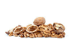 Whole and cracked walnuts, nutshells, kernels. Whole and cracked walnuts with nutshells over kernels isolated on the white background Royalty Free Stock Photo
