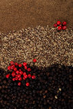 Whole, crashed and ground black and red peppercorns Stock Photo
