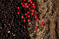 Whole, crashed and ground black and red peppercorns Royalty Free Stock Image