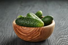 Whole cucumbers in olive dowl on wood table Royalty Free Stock Photography