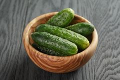 Whole cucumbers in olive dowl on wood table Royalty Free Stock Photo