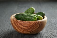 Whole cucumbers in olive dowl on wood table Stock Photo