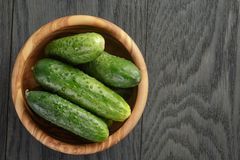 Whole cucumbers in olive dowl on wood table Stock Image