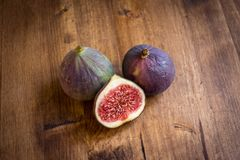 Two whole and a half figs on a wooden table royalty free stock images