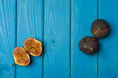 Whole and cut fresh vibrant figs fruit on blue wooden background from above Royalty Free Stock Photography