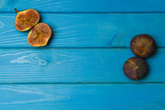 Whole and cut fresh vibrant figs fruit on blue wooden background from above Royalty Free Stock Images