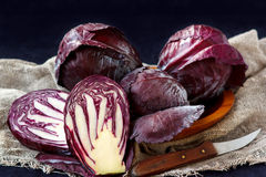 Whole And Cut In Half Fresh Red Cabbage In A Wooden Plate on Dark Background. Close-up Stock Images