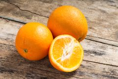 Whole and Cut in Half Orange lying on Weathered Wooden Table Stock Images