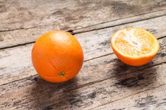 Whole and Cut in Half Orange lying on Weathered Wooden Table Royalty Free Stock Image