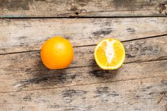 Whole and Cut in Half Orange lying on Weathered Wooden Table Stock Photo