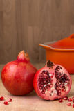 Whole & cut Pomegranate on wood chopping board Punica granatum Royalty Free Stock Images