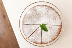 Whole cut sponge cake with icing sugar on glass stand isolated o Stock Photography