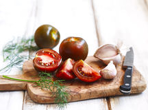 Whole, cut tomatoes and garlic in cutting board Royalty Free Stock Photos