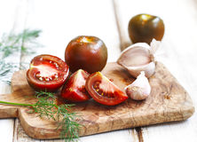 Whole, cut tomatoes and garlic in cutting board Royalty Free Stock Images